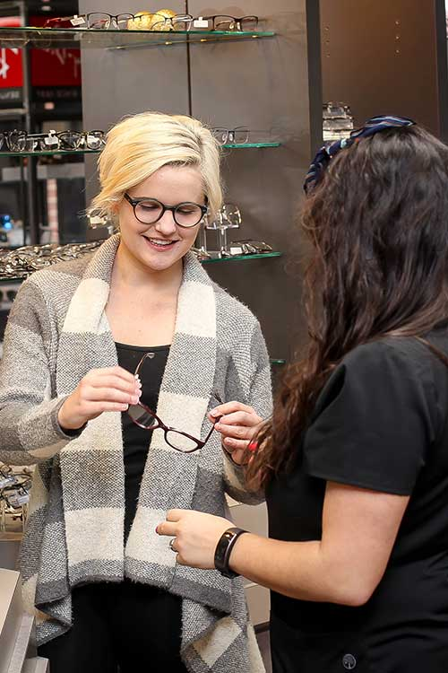 woman taking glasses to try on from optician